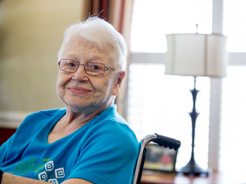 elderly woman with glasses sitting in wheelchair in living room and smiling