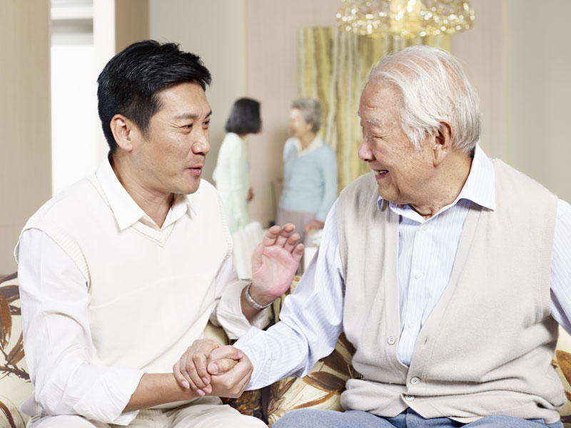 asian man speaking with aging elderly father and holding his hand in room smiling