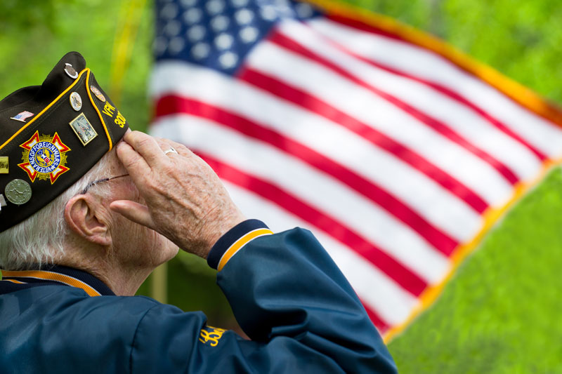elderly vet in uniform saluting american flag outside