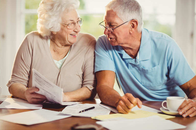 elderly couple going over papers on table doing research and drinking coffee together