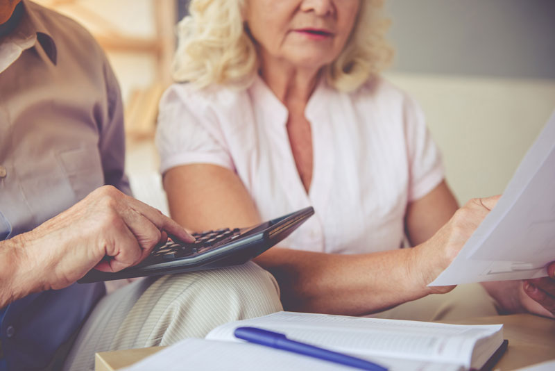elderly couple calculating senior housing cost with calculator and papers