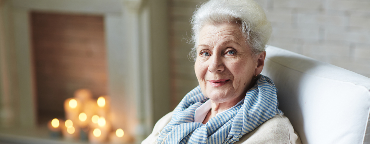 elderly woman wearing blue and white scarf looking at camera and smiling in room with fireplace