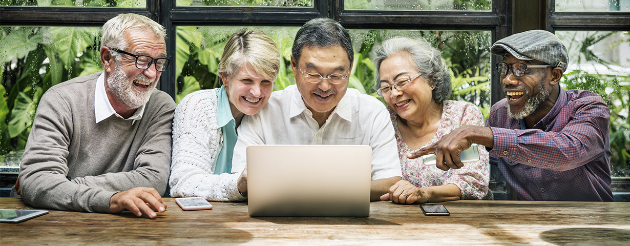 elderly people at table in a row smiling and pointing at laptop with cell phones on table