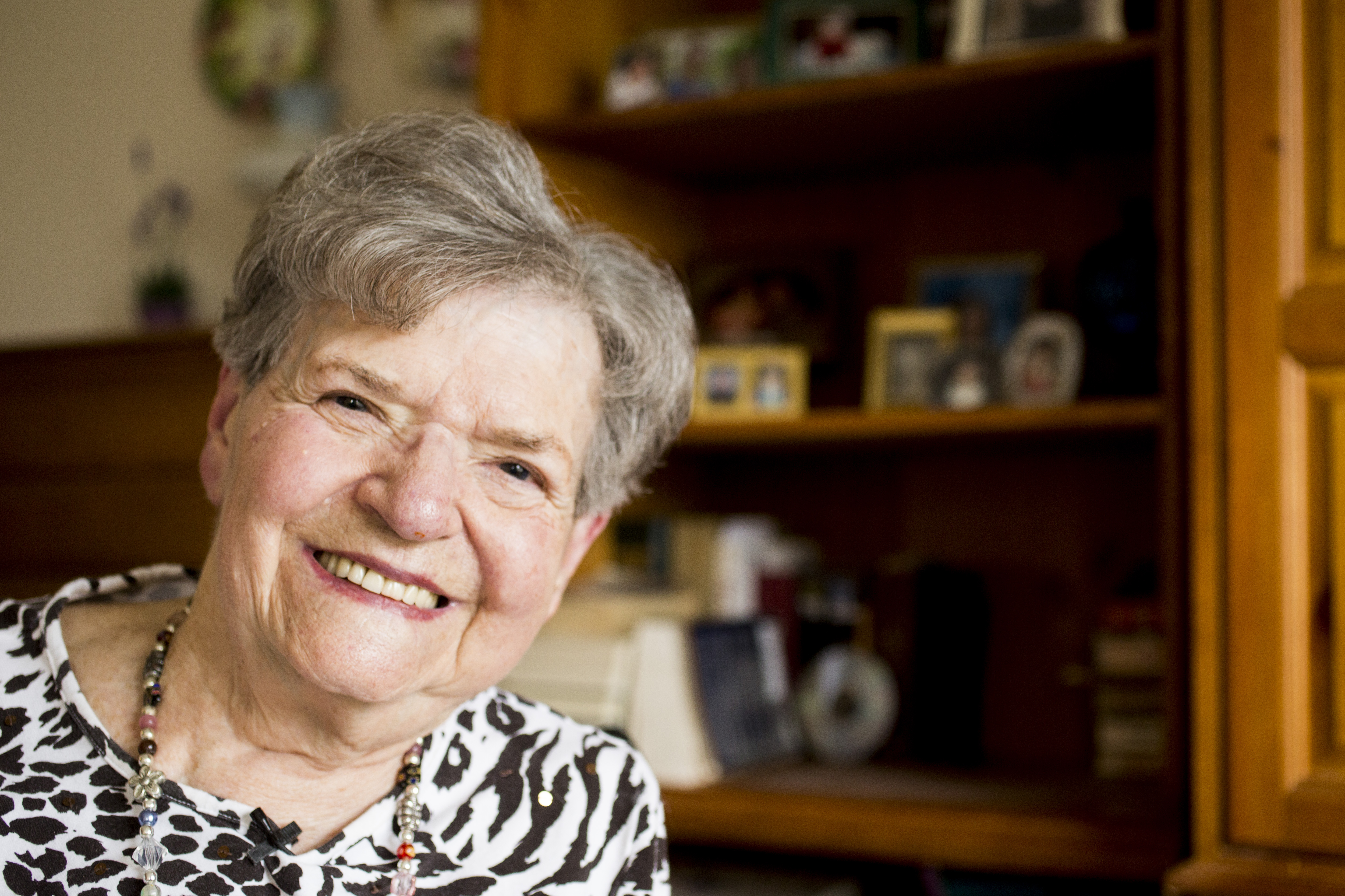 elderly woman smiling at camera in room with bookcase of pictures in background