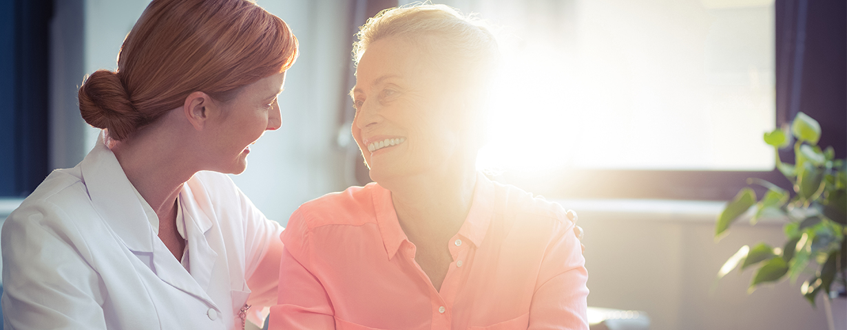 two women smiling together in room with sunlight coming in through window at respite care facility