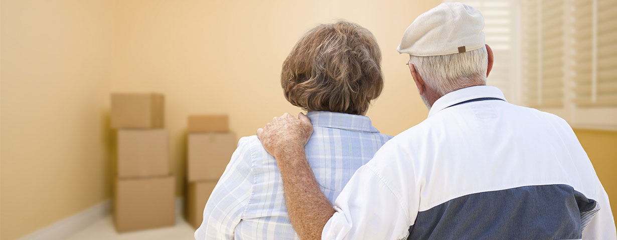 elderly couple looking at empty room with boxes encouraging each other after move