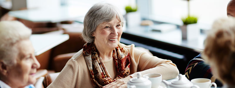 elderly people at table talking and smiling over coffee in cafe