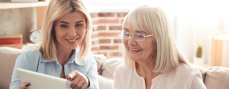 adult child woman explaining something on tablet to elderly mother smiling