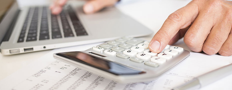 person using calculator and typing on laptop doing taxes