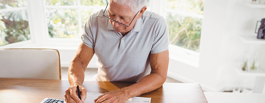 elderly man with glasses going over taxes with calculator in sunny room
