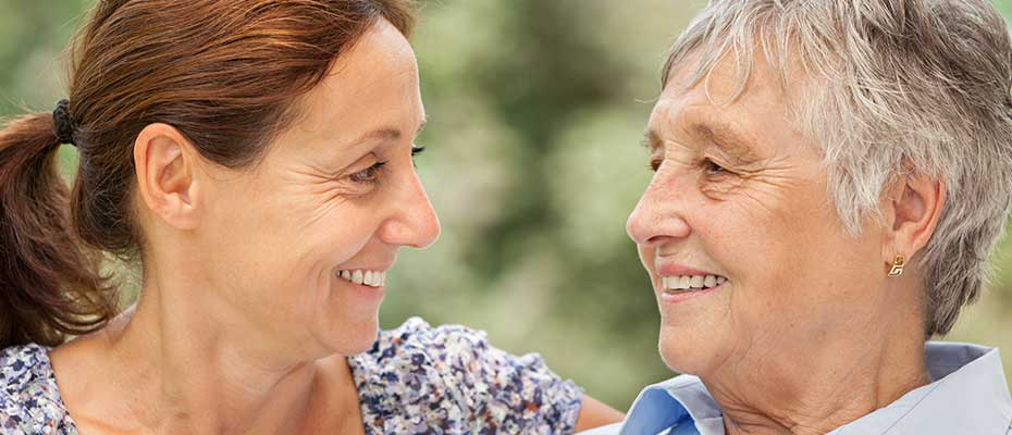 caregiver and elderly woman looking at each other and smiling outside