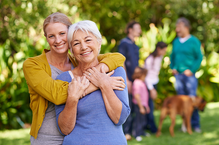 adult child daughter holding elderly mother outside and smiling with family and dog in background