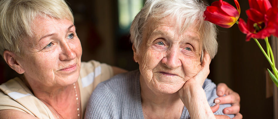 older adult child woman comforting elderly mother as elderly mother looks off into distance
