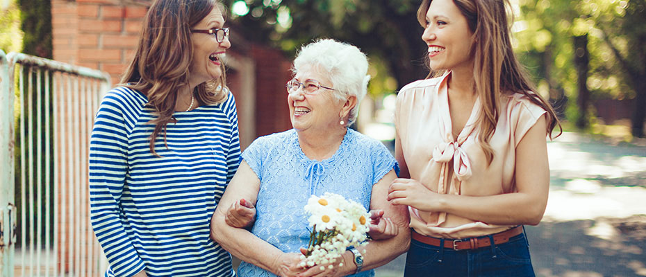 adult children women walking arm in arm with elderly mother holding daisy flowers outside