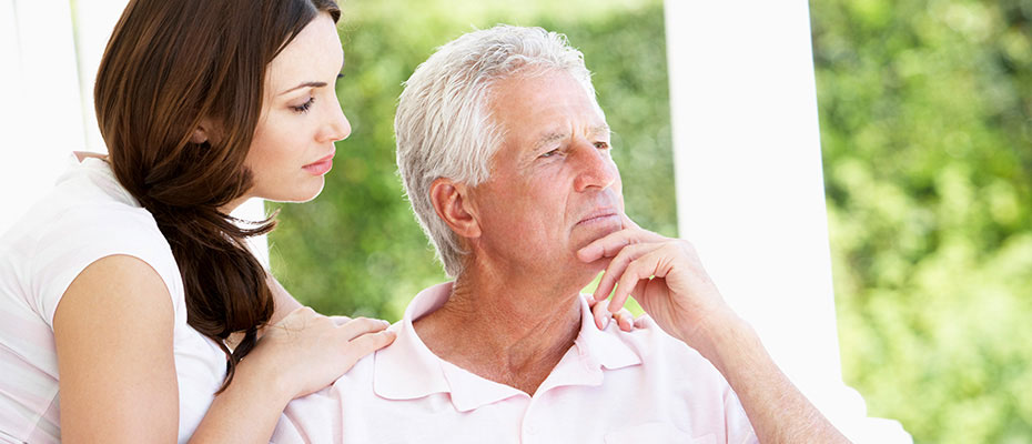 elderly man looking off into distance thinking outside adult daughter comforting