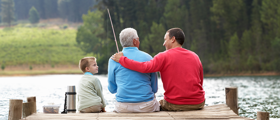 three generations sitting on dock and fishing little boy adult child and elderly man grandfather