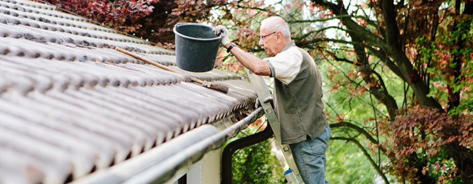 elderly man on ladder outside cleaning debris from roof with bucket and broom