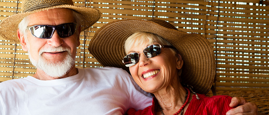elderly couple with sunglasses and sun hats smiling