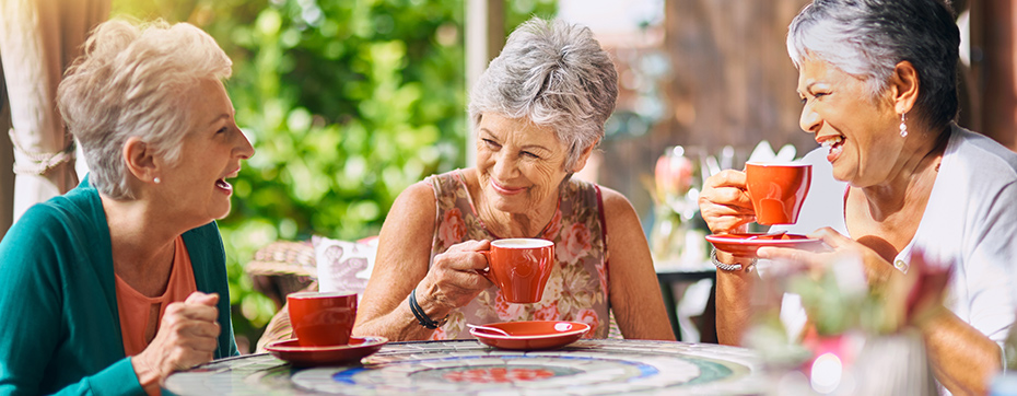 elderly women together laughing and talking outside at table in sunshine while drinking tea coffee