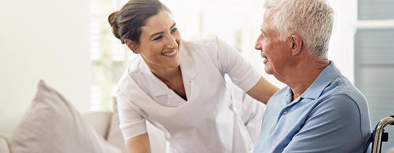 younger skilled nursing care staff member smiling at older man sitting