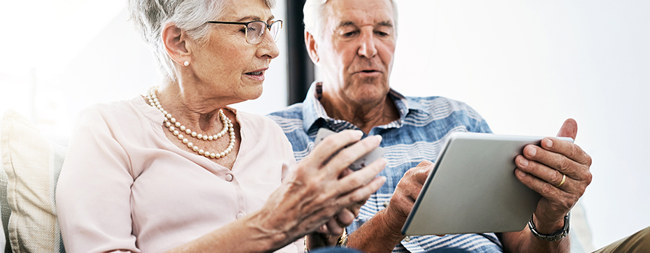 older couple looking at tablet learning costs of aging at home