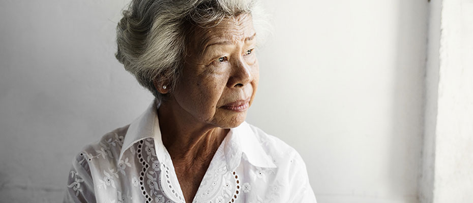 elderly woman showing signs of isolations staring into space and frowning