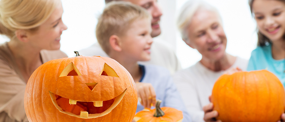 Grandparents carving pumpkins with their grandchildren