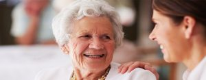 Senior woman talking to her caregiver at a senior living community