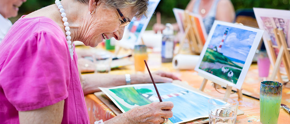 A senior woman painting a water color scene in a painting class