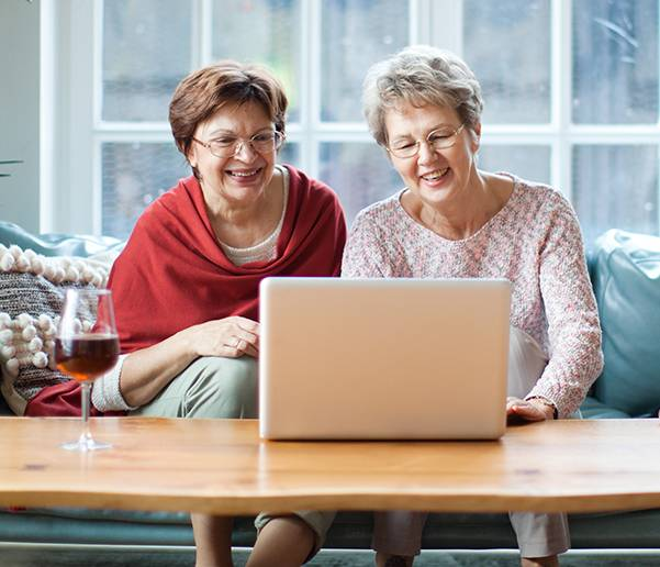 two senior women searching for senior living on a laptop