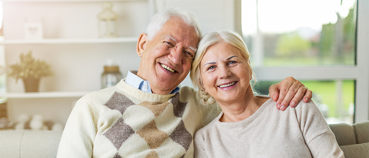 a senior couple smiling and embracing one another
