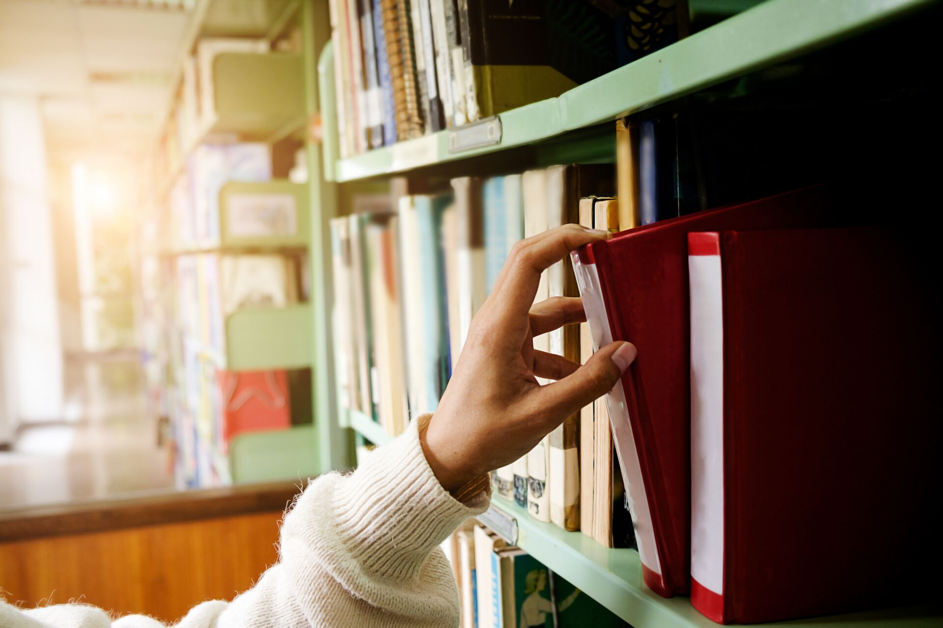 a hand choosing a book of a library shelf