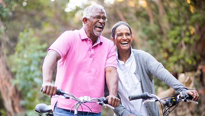 an elderly couple riding bikes outdoors