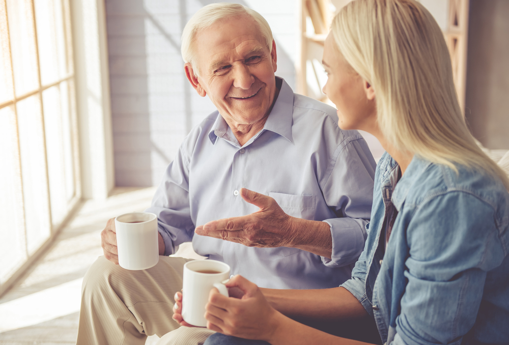 adult woman talking to her aging father about his senior living options