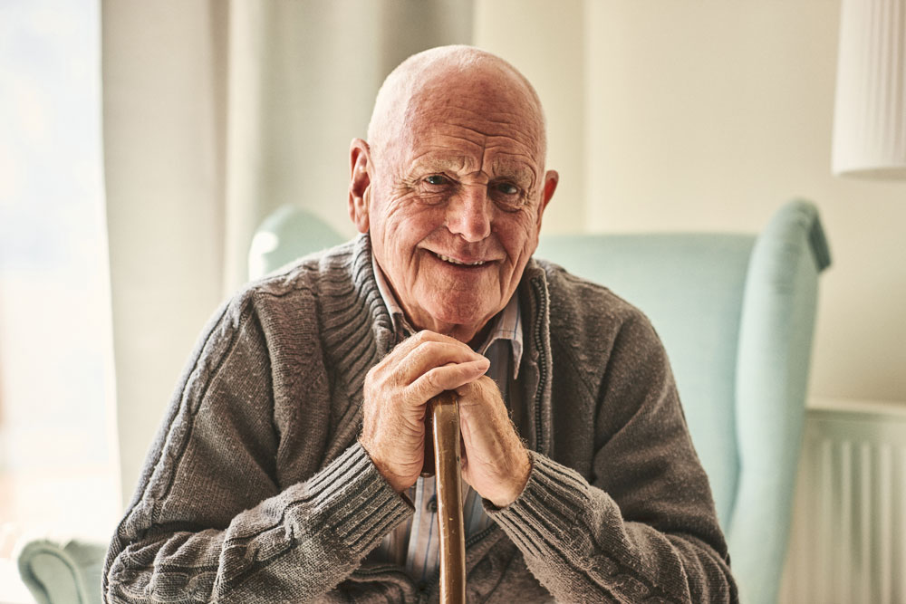 a senior man smiling at the camera while resting his head and hands on his cane