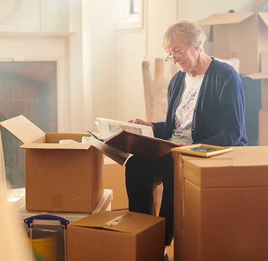 a senior woman looking through her things while surrounded by packing boxes