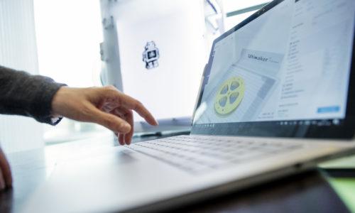 Hand vid dator och 3D-skrivare.