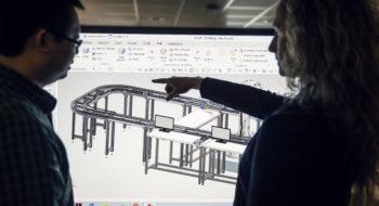 Två forskare vid skärm med produktionslinje som visar optimering.