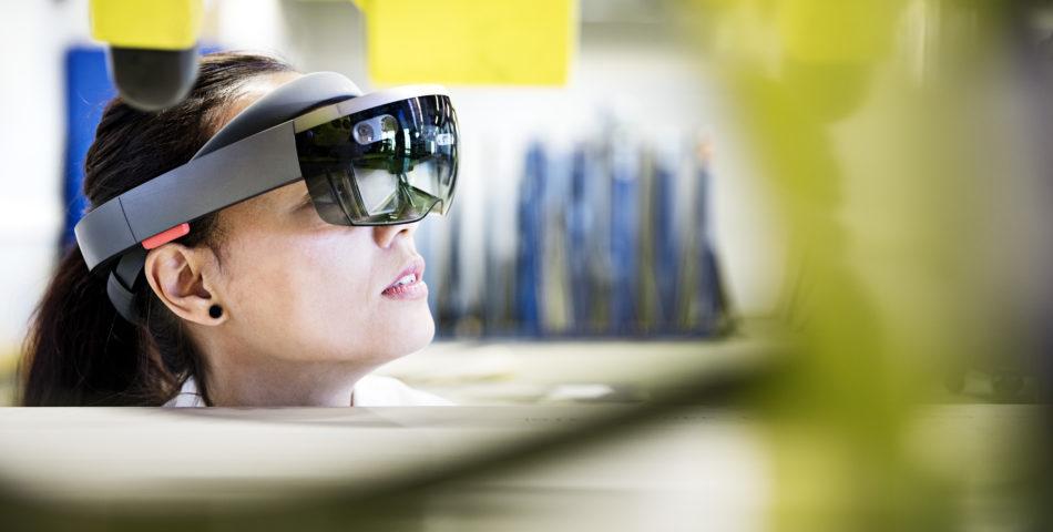 Kvinna i fabrik med VR-glasögon