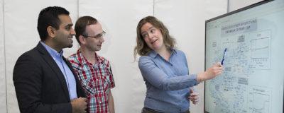 Forskare visar optimering och grafer på skärm.