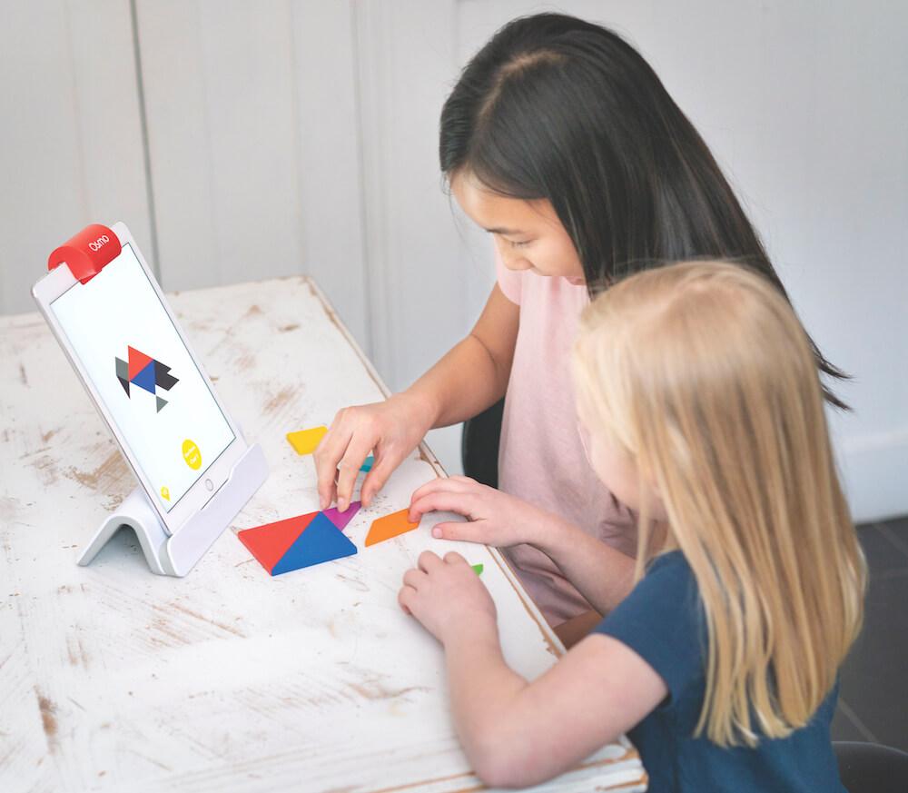 Tangram für Kinder: zwei Mädchen spielen am iPad