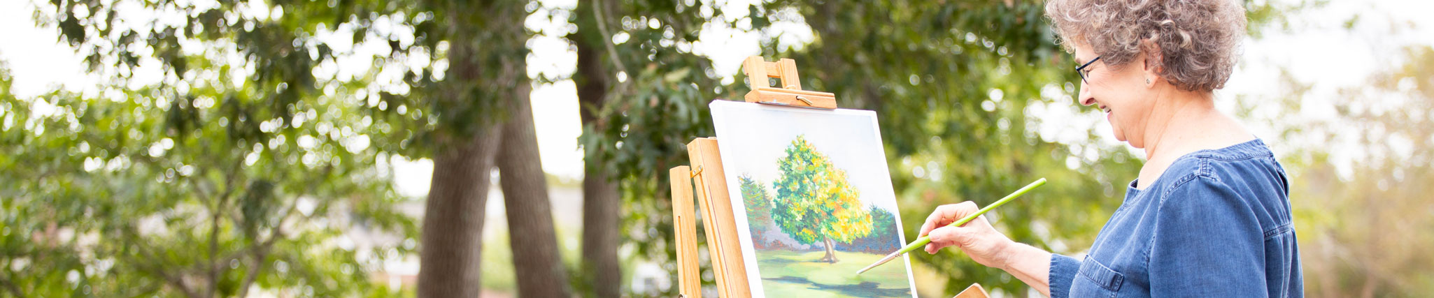 senior lady painting on a canvas outside an independent living community