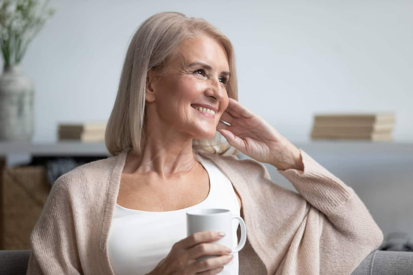 a senior woman smiling while drinking a cup of coffee