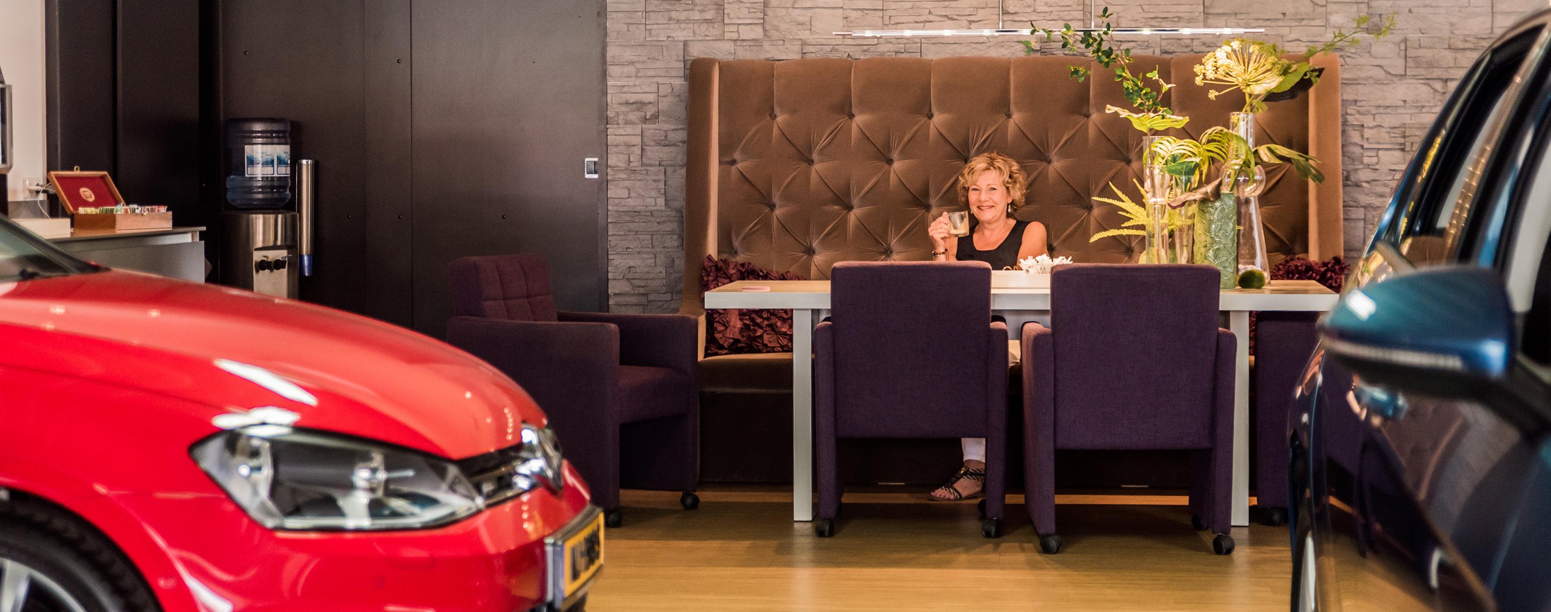 Een klant geniet van een vers kopje koffie bij Auto Koldewijn, terwijl ze op haar auto wacht