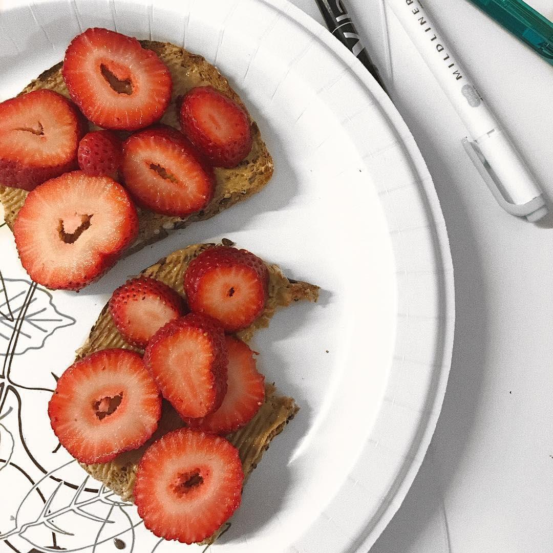 Pan tostado con crema de almendra y fresas picadas