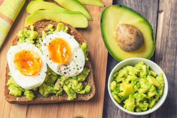 Huevo cocido sobre pan integral, aguacate y rebanadas de jitomate