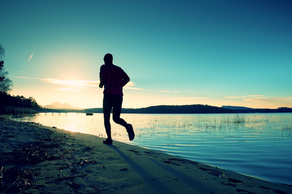Man running along beach as sun rises being healthy working Anywhere