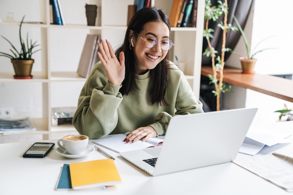 Woman waving at colleagues working in different time zones
