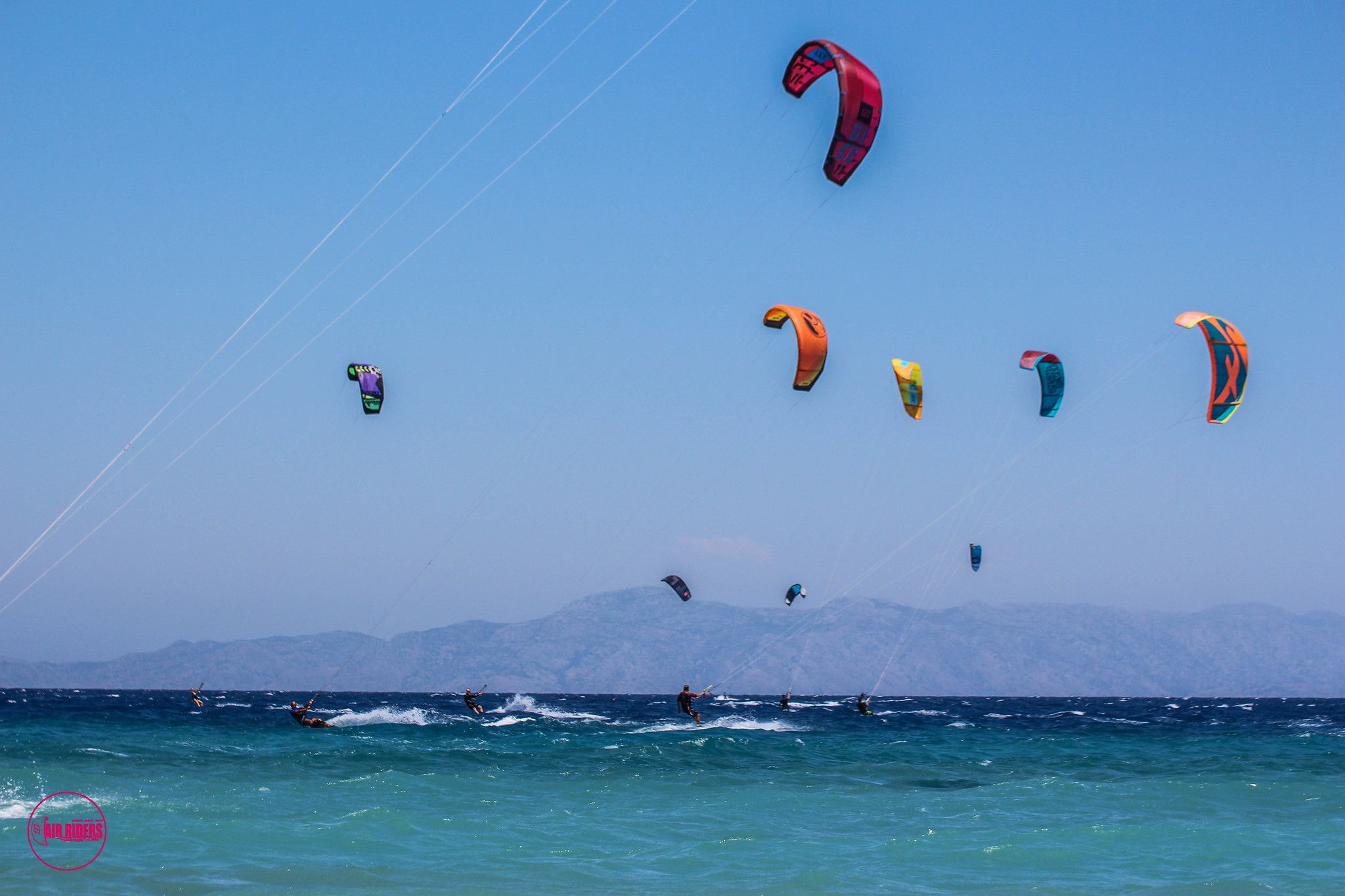 Many kitesurfers in the blue seas of Rhodes