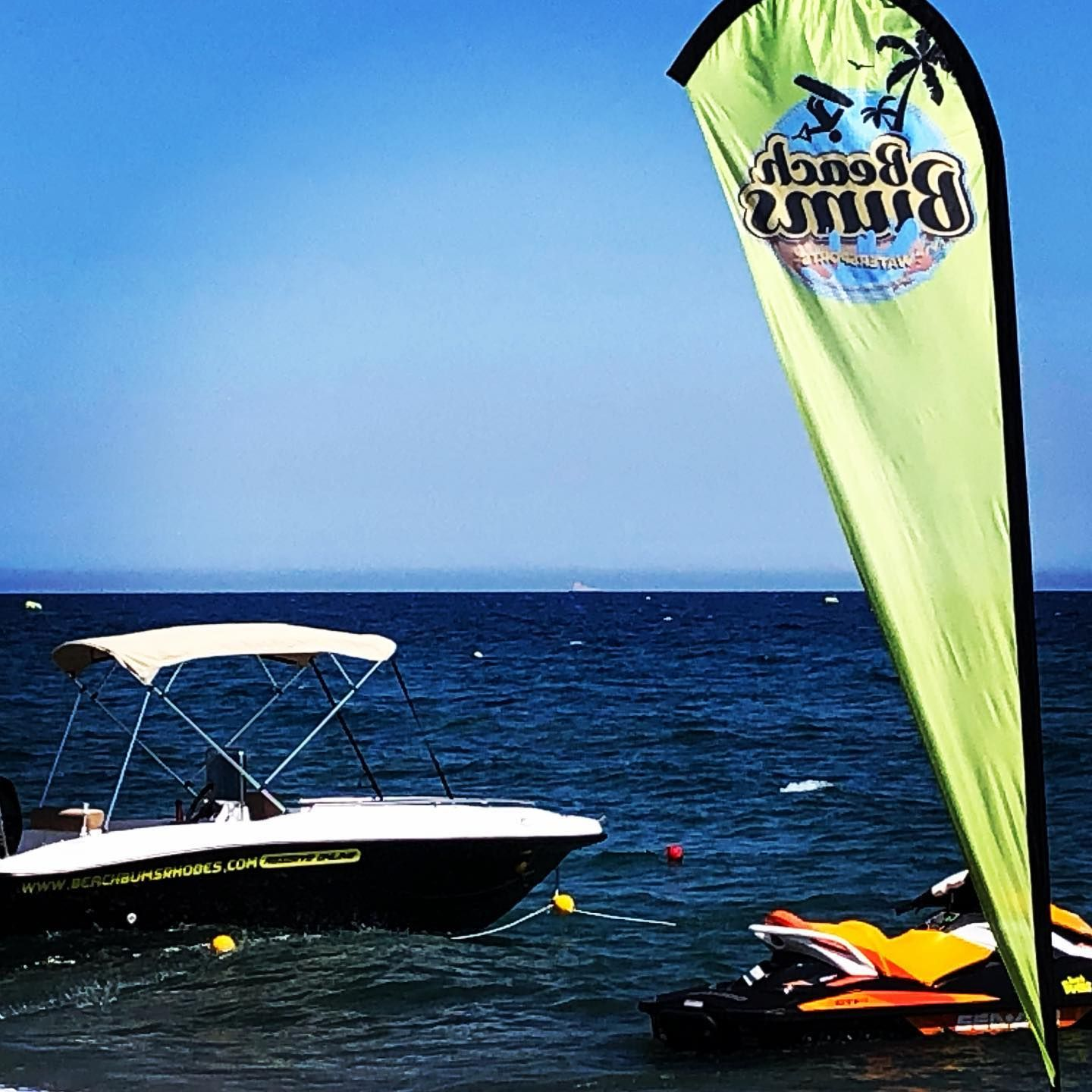 View of rental boat and jetski in the sea with green Beach Bums Rhodes flag on beach